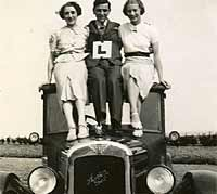 Three people and a vintage Austin motor-car