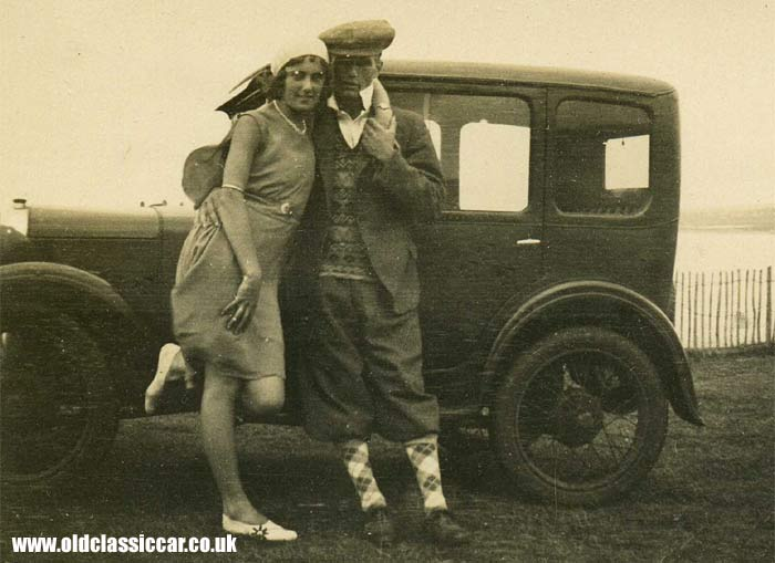 Lady and man stood alongside their Austin motor-car