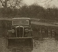 A classic Morris car parked in a river