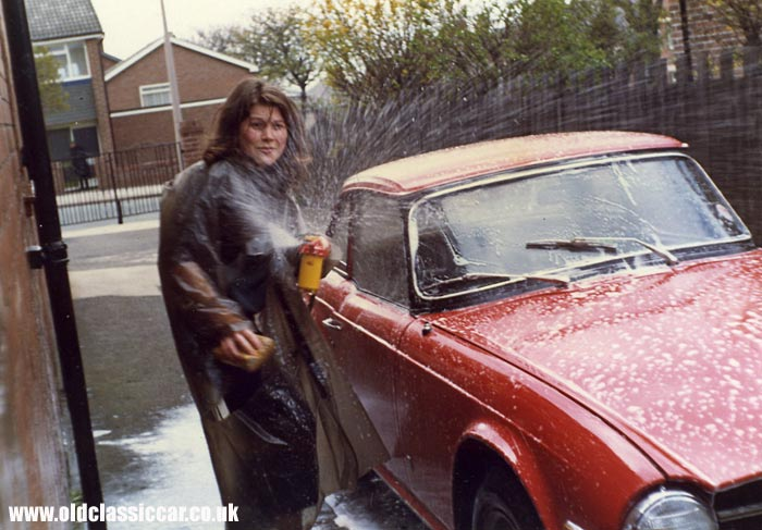 Red Triumph sportscar being washed in the 1970s