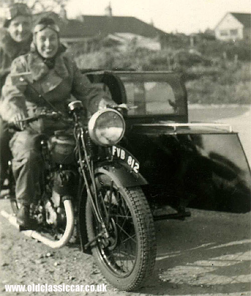 A couple sat on their motorcycle/sidecar combination