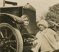 A child tries the vintage car's starting handle