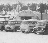 Line-up of Bedford campers outside a garage
