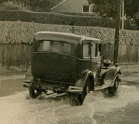 A car drives along a flooded street