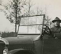 A man sat in a Model T tourer