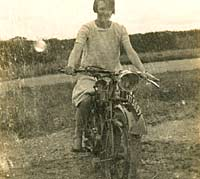 A lady sat on her vintage motorcycle