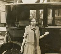 A girl stood with a 1920s car