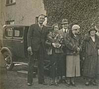 Men and women with a 1920s car