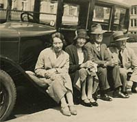 Two women and two men sat on a car's running board