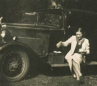 Lady drinks a cup of tea with her 1930s Rover car