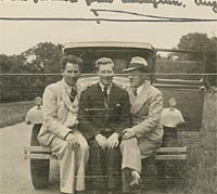 Three men sat on the front of a vintage car